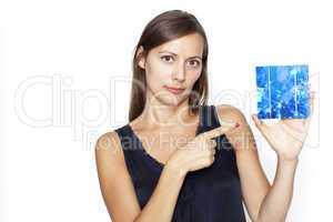 Hübsche Frau zeigt mit Finger auf eine Solarzelle