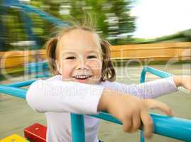 Cute little girl is riding on merry-go-round