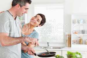Woman smiling at her pan-holding husband