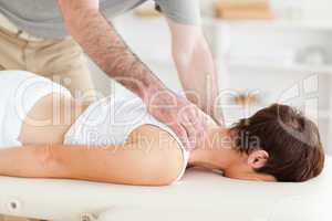 Masseur massaging a woman's neck