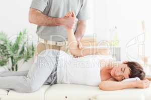 Chiropractor stretches a woman's arm