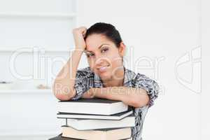 A young student is leaning on books