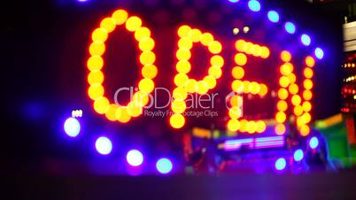 Glowing open neon display sign in a window, rack focus with reflection