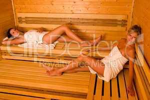 Sauna two women relaxing lying wrapped towel