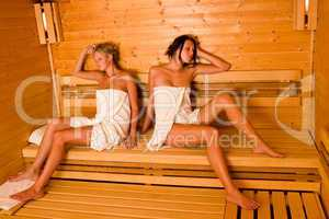 Sauna two women relaxing sitting wrapped towel