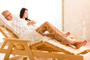 Luxury spa two women relax sitting sun-beds