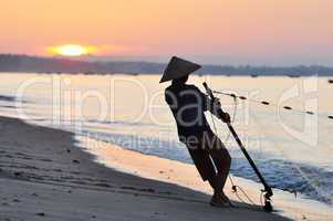 Silhouette of a fisherman on beach at sunrise