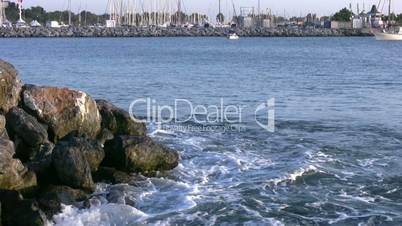 Wave and sailboats in marina