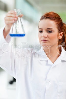 Portrait of a science student looking at a blue liquid