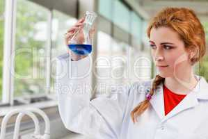 Chemist looking at a blue liquid