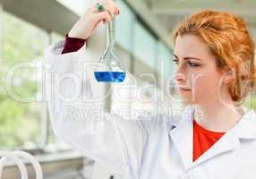 Cute scientist holding a blue liquid