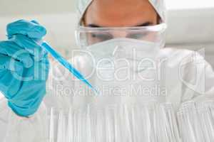 Protected female scientist dropping a blue liquid in a test tube
