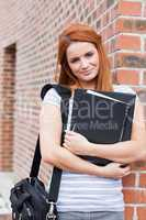 Portrait of a smiling student holding her binder