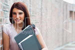 Happy student holding her binders
