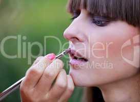 Makeup master applying lipstick
