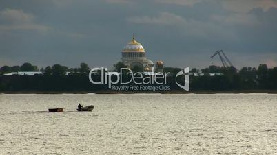 boat floats on the background of the Naval Cathedral of St. Nicholas
