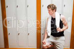 Handsome young sports student leaning on a locker