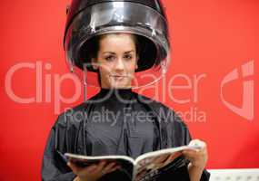 Young woman under a hairdressing machine