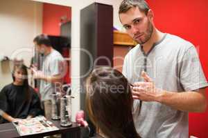 Serious male hairdresser cutting hair
