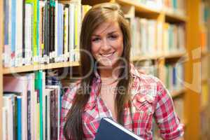 Smiling female student holding a book