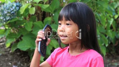 Little Asian Girl Talking On Cell Phone