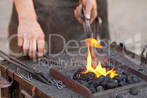 embers, fire, smoke, tools and the hands of a blacksmith