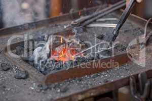 embers, fire, smoke and blacksmith tools