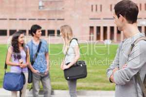 Student looking at his classmates talking