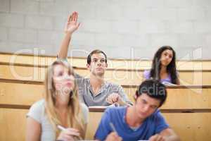 Student raising his hand while his classmates are taking notes