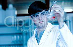 Male scientist looking at an Erlenmeyer flask