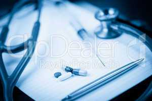 Note pad with stethoscope and pen along with  serynge and capsul