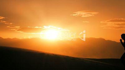 Female Watching the Sun Setting on her Desert Hike