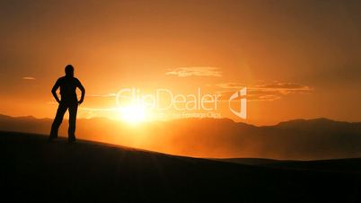 Hiker in Silhouette Completing a Desert Hike