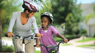 Ethnic Mother & Daughter Bike Riding Together