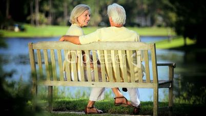 Content Senior Couple Relaxing on Park Bench