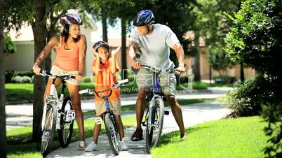 Young Ethnic Family Cycling Together