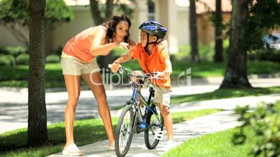 Young Ethnic Mother Encouraging Son on Bicycle