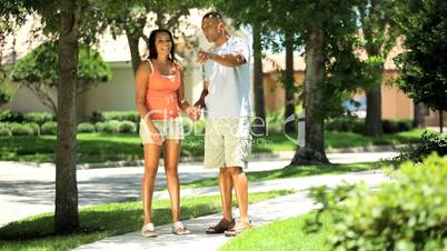 Young Ethnic Couple Looking at Suburban Homes