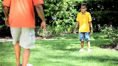 Ethnic Father & Son Kicking a Ball Together