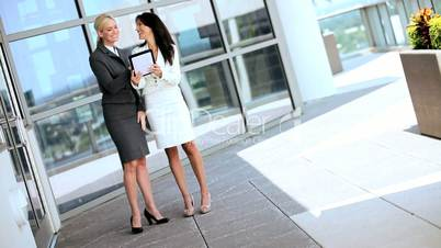 Two Businesswomen Using Wireless Technology Outdoors