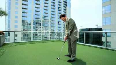 Young Executive Practicing Golf on Office Rooftop