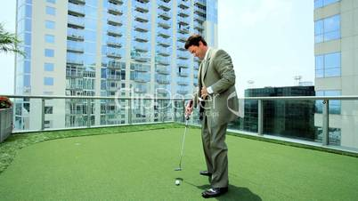 Young Businessman Practicing Golf on City Office Roof