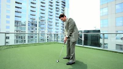 Young Businessman Practicing Golf on Office Rooftop