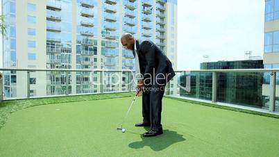Ethnic Businessman Practicing Golf on City Office Roof