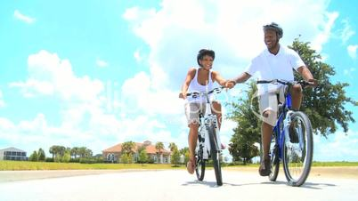 Young Healthy Ethnic Couple Cycling Together