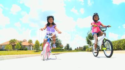Two Young Ethnic Sisters Riding Their Bicycles