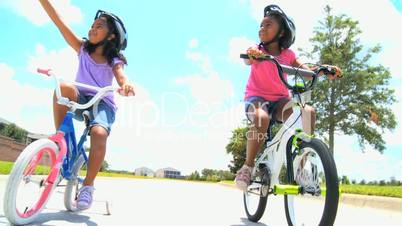 Young African American Sisters Cycling Outdoors