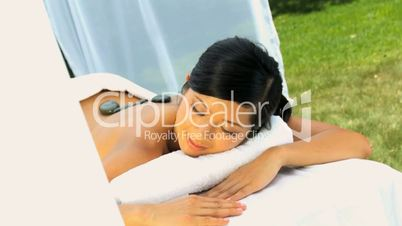 Young Asian Girl Relaxing with Hot Stone Massage