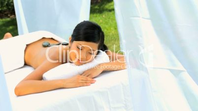 Female Spa Client Receiving Hot Stone Therapy