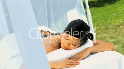 Female Spa Client Relaxing with Hot Stone Therapy